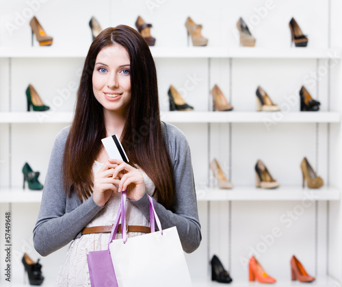 Lady holds credit card in footwear shop