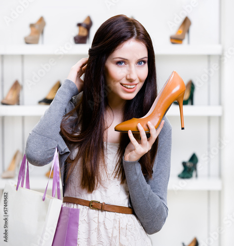 Portrait of woman handing brown leather heeled shoe