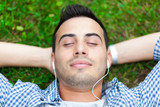 Relaxed young man listening to music on the grass