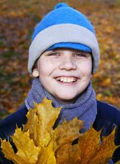 Мальчик с осенними листьями на природе