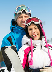Portrait of couple embracing skiers with skis in hands