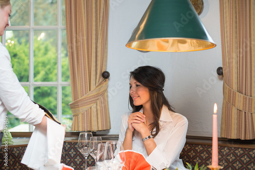 Waitress showing wine bottle to female client