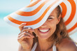 Leinwanddruck Bild - Portrait of happy young woman in swimsuit and beach hat