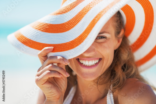 Leinwanddruck Bild Portrait of happy young woman in swimsuit and beach hat