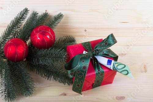 Weihnachtsgeschenk mit Geldschein und Tannenzweig