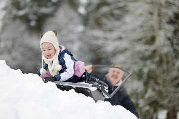 Winter fun: a girl having a ride on a snow shovel