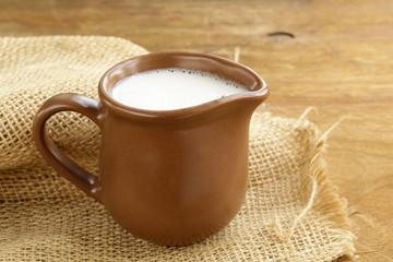 ceramic brown  jug full of milk, rustic style