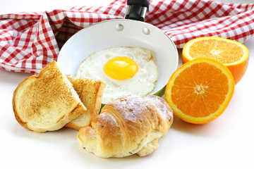 Continental breakfast - croissant, fried egg, toast and oranges