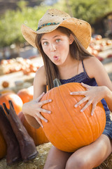 Preteen Girl Holding A Large Pumpkin at the Pumpkin Patch.