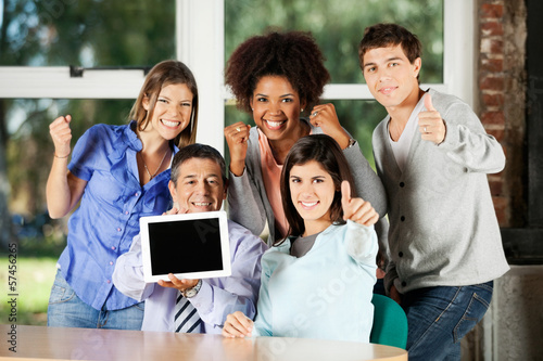 Teacher Holding Digital Table With Students Gesturing In Classro