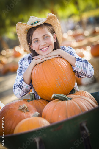 Preteen Girl Playing with a Wheelbarrow at the Pumpkin Patch.
