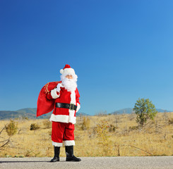 Full length portrait of a Santa claus with bag standing on a roa
