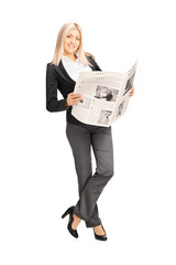 Young businesswoman holding a newspaper and leaning against wall
