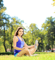 Young female athlete sitting on a grass and holding a bottle, in