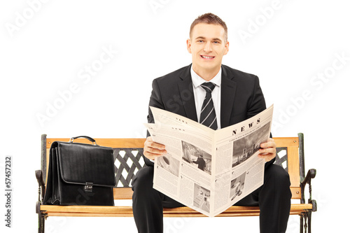 Young businessman sitting on a wooden bench with newspaper
