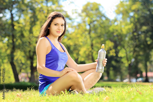 Young female athlete sitting on a grass and holding a bottle