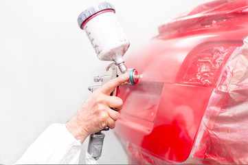 auto engineer paiting a red paint on modern car in special booth