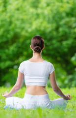 Backview of woman who sits in asana position zen gesturing