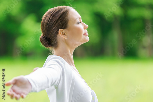 Profile of girl with outstretched arms and closed eyes