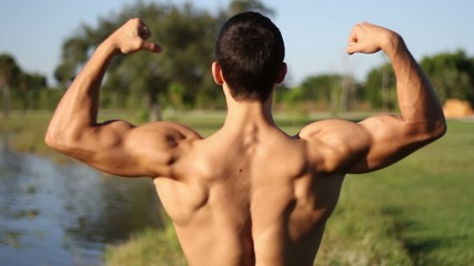 Flexing back muscles. bodybuilder. outdoors