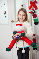 Girl With Santa Toy Standing At Home