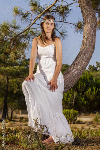 girl with a long white dress on the forest.
