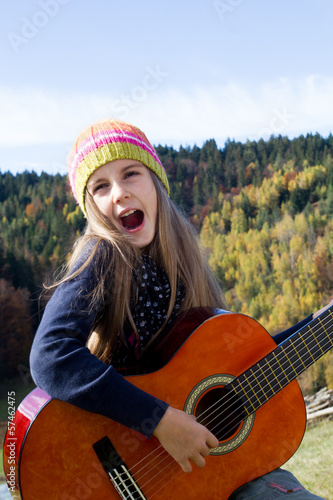 Happy little girl playing a guitar outdoor