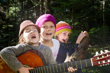 Group of children singing and playing guitar together in the for