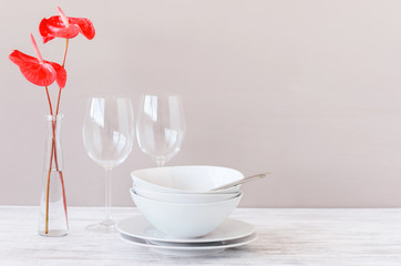 Minimalistic table setting with plain crockery and red flowers
