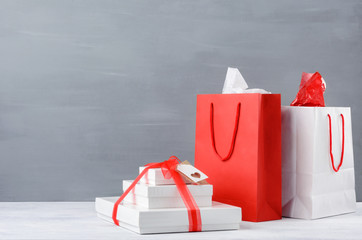Red and white shopping bags and gift boxes on table