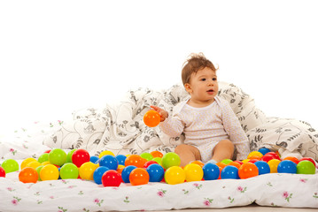 Baby playing with balls in bed