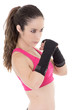 Female mixed martial arts fighter in MMA style gloves strikes a
