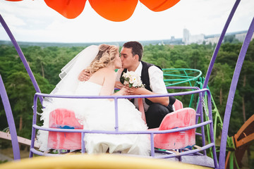 Newly married couple riding on Ferris wheel and kissing