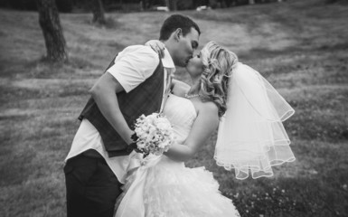 handsome groom passionately kissing bride in park