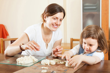 Young woman and her child sculpting from clay or dough in home