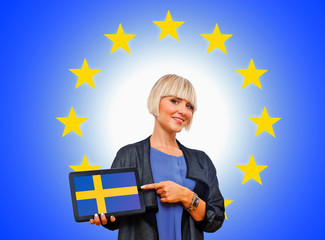 woman holding tablet with sweden flag on european union backgro
