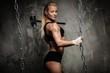 Beautiful muscular bodybuilder woman holding hammer