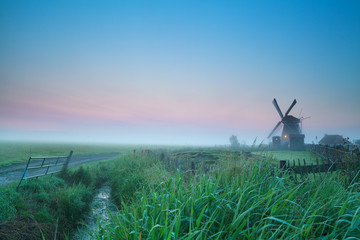 sunrise over Dutch farmland with windmill
