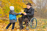 Young child giving an elderly man autumn leaves