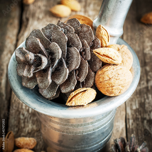 Pine Cones, Walnuts and Almonds in a mortar on wooden background