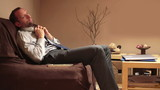 Tired businessman after work relaxing in front of tv in home