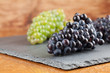 Blue and green grape clusters on slate board