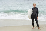 Female surfer in wetsuit with surfboard by beach, portrait