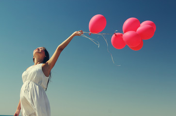 Young pregnant woman holding red balloons. Photo in old color im