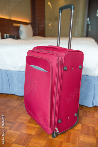 red suitcase stands up inside a hotel room