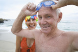 Mature woman in swimming costume and cap smiling by man with goggles, portrait