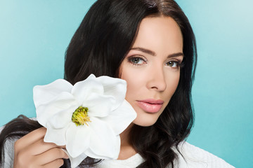 portrait of attractive brunette woman holding white flower