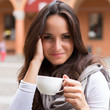 beautiful young girl drinking coffee in a old town cafe