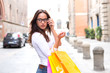 Beautiful woman with glasses carrying shopping bags