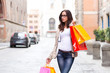 Beautiful girl with glasses carrying shopping bags